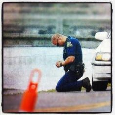 Louisiana State Trooper at his knees praying for the family that lost two young juveniles in Ascension Parish.