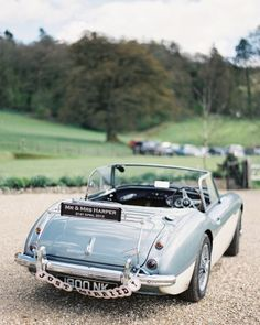 """The newlyweds decorated their getaway car, an old Austin Healey 3000, with a custom license plate that read """"Mr and Mrs Harper 21st April 2012"""" and """"just married"""" cards strung with ribbon by the bride."""