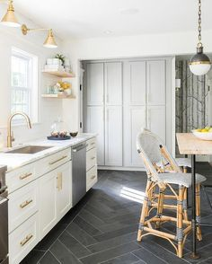 White and gold kitchen features white shaker cabinets adorned with brass hardware paired with calcutta marble countertops and a white subway tile backsplash facing a wall of floor to ceiling gray cabinets painted Benjamin Moore cape May Cobblestone.