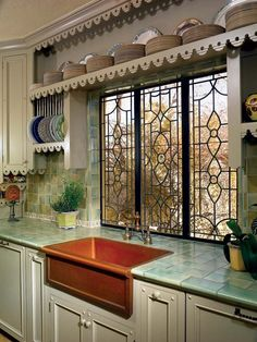 This stunning kitchen remodel has custom designed leaded glass windows, copper farmhouse sink, salvaged tile backsplash,  and custom cabinets with scalloped trim.