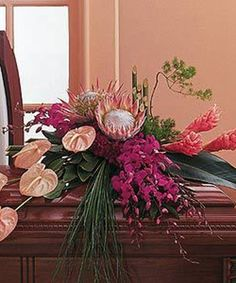 This stunning and unique arrangement of tropical flowers in soothing pinks and purples makes an eloquent statement of love and support. This half-couch casket spray arrives styled with anthuriums, ginger, dendrobium orchids and exotic protea, along. Tropical Flower Arrangements, Funeral Flower Arrangements, Ikebana Arrangements, Beautiful Flower Arrangements, Funeral Flowers, Beautiful Flowers, Simple Flowers, Casket Flowers, Table Flowers
