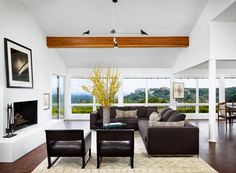 exposed beam + steel grey sectional + white walls in living room by mark ashby design