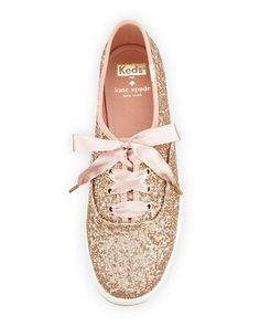 "kate spade new york glitter covered canvas sneaker. 0.8"" flat heel. Round toe. Lace-up front. Logo patch stitched at tongue. Spade stud and Keds logo at back. Canvas lining and cushioned insole. Rubbe"