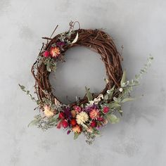 Sprays of eucalyptus and pussy willow lend beautifully wild silhouette to this grapevine wreath, each one accented with a cluster of strawflowers, gom