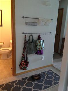 Small entryway organization using Ikea kitchen organization rods, small strainer, buckets, and hooks.