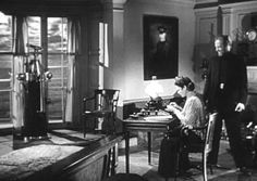 """Lucy Muir typing """"Blood & Swash"""" in her bedroom at Gull Cottage - the captains painting hangs on the wall"""