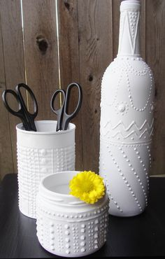 one glass bottle, one glass jar and one can painted with three dimensional craft paint and spray painted white