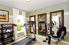 Three rustic mirrors and crisp stripes of mint, white and taupe paint make a sunny exercise room. The Gray Myst Model by DiVosta Homes  in Naples, FL.