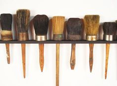 A collection of Antique Carpenters Brushes mounted on a custom maple display shelf
