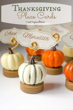 Thanksgiving Place Card Holders - small wooden discs or wheels from the doll-making section for a base, styrofoam pumpkins from seasonal vase filler, card holders curled free-handed from dollar store floral wire, and homemade name cards for place settings!