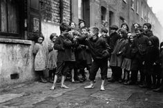 These stunning black and white pictures show the history of young children playing sports on the streets of London. Without the technology of today, these images dating back to the 1920s show young friends entertaining themselves with a simple pair of dice or a ball and piece of chalk to mark out a set of goalposts. One of the earliest pictures, taken in December 1920 in Shadwell, shows two boys boxing barefoot in the street watched by a crowd of their friends.
