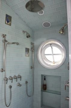 Round window that tilts open! Crazy amount of shower nozzles & controls, but tiling up to & including the ceiling I like.