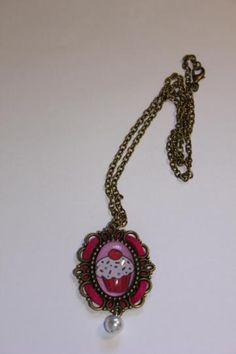 Collar color bronce con un camafeo con la imagen de un cupcake y rodeado de ante/terciopelo rosa, y una perla abajo como adorno. - See more at: http://lookestilo.com/portfolios/artesania-mr/productos/collar-bronce-camafeo-cupcake#sthash.AAAUHTFV.dpuf