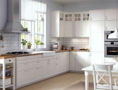 Traditionellt kök med vita skåp, bänkskivor i trä, vitrinluckor och integrerade vitvaror