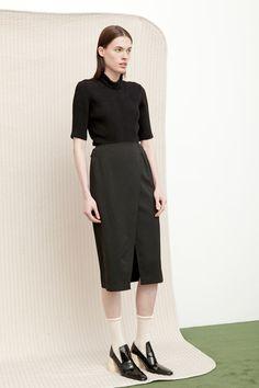 Madeleine Skirt in black twill worn over Jules Bodysuit in black ribbed viscose blend.