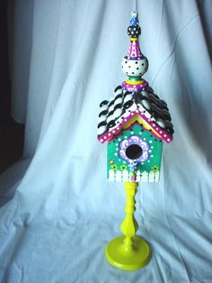 handpainted birdhouse on stand with a beaded roof