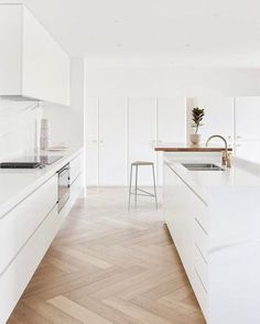 All white minimalist kitchen with natural wood floors