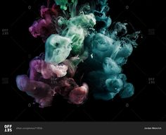 Purple, green, and blue smoke come together on a black background ...