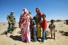 A member of the UN Mission for the Referendum in Western Sahara (MINURSO)'s Military Liaison Office chats with a group of Western Saharans