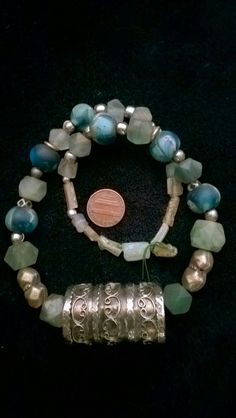 Roman glass, Afghan hexagon bluish green amethysts, old blue face glass beads from Nepal, two old and very rare afghan metallic beads, and a BIG focal barrel beads with a very interesting work. $56