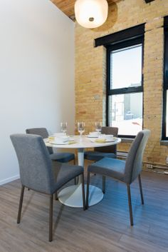 The LOMBARD at District Condos - Loft style conversion condos featuring exposed brick, century old wood beams, 14 ft ceilings and modern finishes. Saarinen table, modern grey chairs