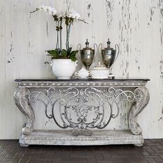 This massive console table is a personification of strength with ornate cast stone, forged iron, and aluminum casting detail with a burnished finish. A penshell border adds the finishing touches to its black fossil stone top. #ambellahome #console #sofatable #furniture