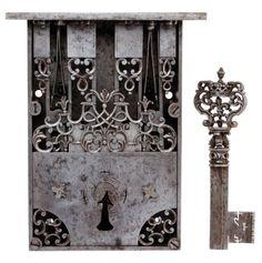 Remarquable serrure de maîtrise et sa clef Modèle pour coffre, en fer forgé et sculpté. Mécanisme à deux gâchettes.  Clef à bossette formée de quatre dauphins en console. L'anneau figure une fleur de lys timbrée d'une couronne de marquis et entourée de deux esses. Tige forée en tiers-point cannelé.   France XVIIe siècle Serrure – H : 17,5 – L : 11,2 cm Clef – H : 13,8 cm