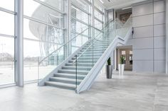 Modern staircase design at University building Featuring stylish grey concrete tiles. Large windows.