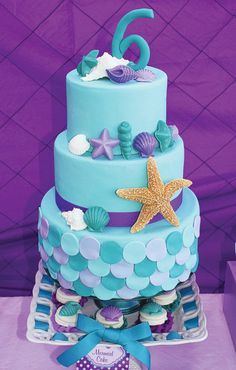 A Little Mermaid Party with Ariel cookie favors, DIY floating jellyfish, mermaid tail topped cupcakes, Clam + Seahorse lollipops + a teal and purple cake