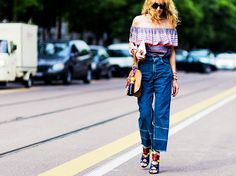 A striped off-the-shoulder top is worn with high-waisted denim culottes, colorful sandals, and a wristlet bag