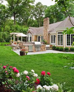 Gorgeous landscaping makes this backyard a retreat to be enjoyed year-round. A Spanish-influenced patio features a built-in cook station with a stainless steel grill, a covered dining table and pergola-shaded lounge chairs.