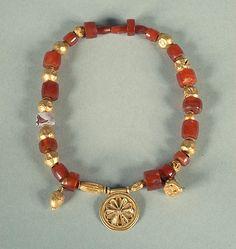 5-6th C. BCE. Phoenician Gold and carnelian quartz necklace.  Central round gold medallion a twelve petals design; flanked by a gold amphora and a ram`s head pendant. Necropolis. tomb D, Cádiz. Spain.