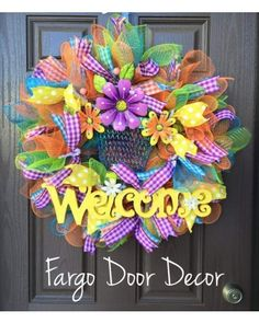 Bright and Colorful Spring Welcome wreath. Filled with Green, Blue and Orange mesh. Polka dots and plaid ribbons throughout.