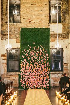 Brides.com: 15 Stunning Wedding Flower Walls A boxwood hedge studded with bright blooms is a colorful way to mark the ceremony spot (and how pretty is that petal-strewn aisle?!). Created by Bear Flag Farm.Photo: Elizabeth Messina