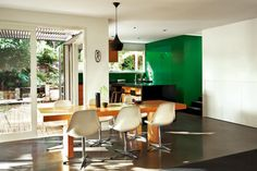 Polished concrete flooring in charcoal anchors the dining/kitchen area. love the punch of emerald green wall.