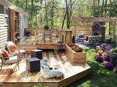 Fascinating Backyard Deck Designs With Half Fence Deck And Half Flat Deck Using Wooden Material And Also There Is A Small Fireplace In The Corner Of Yard