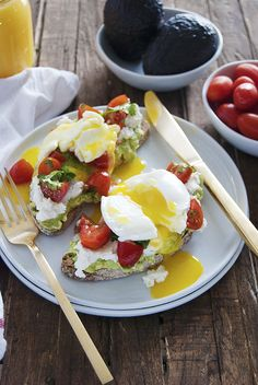 This smashed avocado toast recipe features creamy avocado with fresh ricotta, a cherry tomato salad, and delicious poached eggs.