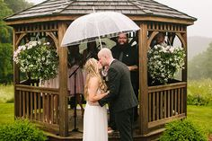 The rain certainly didn't dampen this outdoor wedding, but rather created a cute rainy wedding photo. The ceremony site's gazebo shielded the wedding party as the bride and groom shared a kiss under an umbrella. | Jamie & Josh's Sweet Spencer, MA Real Wedding by Zac Wolf Photography #myweddingmag