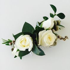 Modern bridal floral hair comb featuring white roses with lush green foliage and berries. #bride #weddingflowers #hairpiece #flowercomb #white #rose