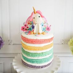 Pastel Unicorn Birthday Party. Love this rainbow cake and the adorable topper! See the party on prettymyparty.com