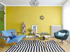 Salón decorado con estilo retro, años 50, y pared color mostaza
