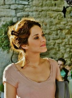 Marion Cotillard: bunned brunette w/ matching eyeshadow, grey satchel, short-sleeve U neck pink blouse w/ matching lipstick
