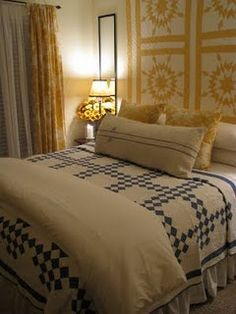 Yellow & white star quilt on the wall & blue & white Irish chain quilt on the bed. I am in love!!