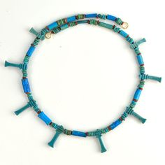 Egyptian Faience Bead and Djed Pillar Necklace, 26th Dynasty, 664-525 BCThe djed symbol is one of the more ancient and commonly found symbols in Egyptian mythology. It is a pillar-like symbol in hieroglyphics representing stability. It is associated...