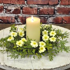 "Add a natural feel to your candle and table with the soothing off-white daisies and calming green ferns in this nature lover's candle wreath! Cheery yellow centers add a touch of sunshine in each mini daisy flower. Accented with shade-garden greens this wreath has just the right mix of sunshine and shadow. Grapevine base. Approximately 12"" diameter, 6"" opening #country #decor #artificial #spring #flowers"