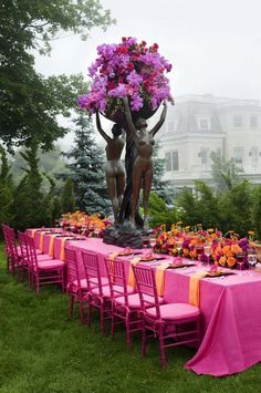 Fuchsia phalaenopsis orchids & Princess roses cascading from bronze statues nestled in a floral &  tangerine runner set on raspberry linen.     wow!