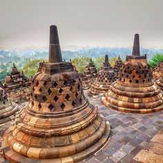 A hazy sunrise atop the fascinating UNESCO World Heritage Site of Borobudur Temple near Yogyakarta, Java, Indonesia is a must do experience in Southeast Asia.