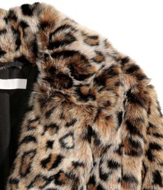 Jacket in soft faux fur with notched lapels, concealed snap fasteners at front, and side pockets. Lined.