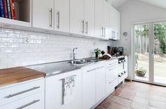 carrelage métro blanc en tant que crédence de cuisine classe, armoires blanches et plans de travail en bois et inox