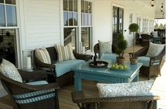 porch - dark brown wicker with blue cushions and table - via Talk of the House